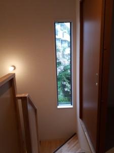 階段の中途の細長い窓は治代さんのこだわり。今満開の百日紅